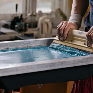 man using silk screening printing